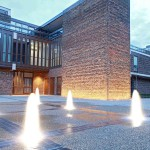 Floor fountains at night in front of a brick building