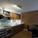 A modern kitchen with exposed brickwork and a dining table