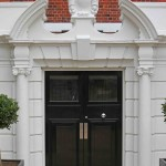 A black front door with a white decorative arch
