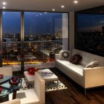 The living room within a showflat with a large window of a city at night